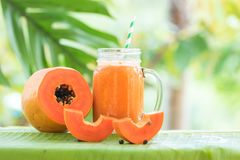 Papaya fruit glass jar with smoothie shake. Tropical exotic papaya fruit and glass jar with smoothie shake juice drink outdoors with palm leaves royalty free stock photography