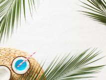 Tropical flat lay with palm leaves and blue cocktail in coconut royalty free stock images