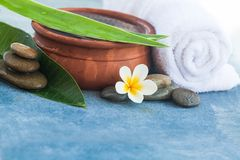 Tropical flower and stones for therapy on blue background.  royalty free stock images
