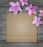 Tropical flowers and bamboo on a wooden background Stock Photography
