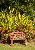 Tropical flowers overwhelm cast iron seat Stock Photography