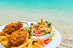 Tropical food of grilled fish, vegetables dish served on tropical island in Aitutaki lagoon, Cook Islands. With selective focus royalty free stock images
