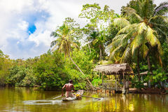 Tropical forest on the river bank .Fisherman floating in a boat. Stock Photo