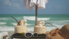 Tropical fresh coconut cocktails in beach cafe with hat, sunglasses, umbrella on a turquoise sea background. slow motion. Tropical fresh coconut cocktail in stock footage