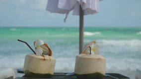 Tropical fresh coconut cocktails in beach cafe with turquoise sea background and changes focus to the sea. 3840x2160. Tropical fresh coconut cocktail in beach stock footage