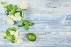 Tropical fresh cold cocktail gin tonic with mint, lime, ice, straw on light blue shabby wood board, border, top view. Tropical fresh cold cocktail gin tonic royalty free stock photography