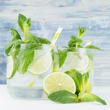 Tropical fresh cold cocktail with mint, lime, ice, straw on light blue shabby wood board, closeup. Tropical fresh cold cocktail with mint, lime, ice, straw on royalty free stock photo