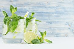 Tropical fresh cold cocktail with mint, lime, ice, straw on light blue shabby wood board, copy space, closeup. Tropical fresh cold cocktail with mint, lime, ice royalty free stock photography