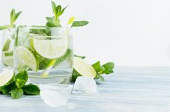 Tropical fresh cold cocktail with mint, lime, ice, straw on light white background, copy space, closeup. Tropical fresh cold cocktail with mint, lime, ice stock photos