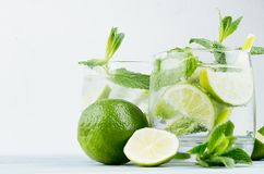 Tropical fresh cold cocktail with mint, lime, ice, straw on light white plaster background, copy space, closeup. Tropical fresh cold cocktail with mint, lime Royalty Free Stock Photo