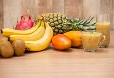 Tropical fresh fruit set and juice smoothies isolated with wooden background royalty free stock photos