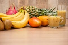 Tropical fresh fruit set and juice smoothies isolated with wooden background royalty free stock images