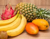 Tropical fresh fruit set and juice smoothies isolated with wooden background. Tropical fresh fruit set and juice smoothies isolated with the wooden background royalty free stock photography