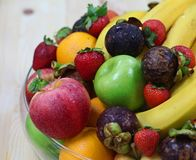 Tropical fresh fruits. Tropical assorted fresh fruits in a glass display bowl royalty free stock photo