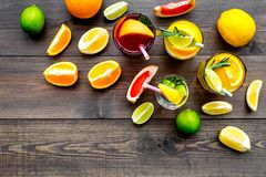 Tropical fruit cocktail with alcohol. Glass with beverage near oranges, grapefruit, lime and rosemary on dark wooden. Background top view Royalty Free Stock Photo