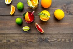 Tropical fruit cocktail with alcohol. Glass with beverage near oranges, grapefruit, lime and rosemary on dark wooden. Background top view Stock Image