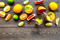 Tropical fruit cocktail with alcohol. Glass with beverage near oranges, grapefruit, lime and rosemary on dark wooden. Background top view Royalty Free Stock Photography