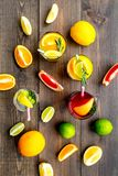 Tropical fruit cocktail with alcohol. Glass with beverage near oranges, grapefruit, lime and rosemary on dark wooden. Background top view Royalty Free Stock Images