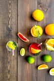 Tropical fruit cocktail with alcohol. Glass with beverage near oranges, grapefruit, lime and rosemary on dark wooden. Background top view Stock Images