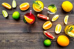 Tropical fruit cocktail with alcohol. Glass with beverage near oranges, grapefruit, lime and rosemary on dark wooden. Background top view Stock Photo