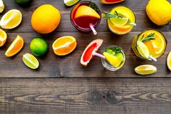 Tropical fruit cocktail with alcohol. Glass with beverage near oranges, grapefruit, lime and rosemary on dark wooden. Background top view Stock Photography
