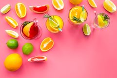 Tropical fruit cocktail with alcohol. Glass with beverage near oranges, grapefruit, lime and rosemary on pink background. Top view Stock Photos