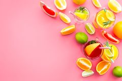 Tropical fruit cocktail with alcohol. Glass with beverage near oranges, grapefruit, lime and rosemary on pink background. Top view Royalty Free Stock Photo