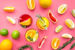 Tropical fruit cocktail with alcohol. Glass with beverage near oranges, grapefruit, lime and rosemary on pink background. Top view Royalty Free Stock Photos
