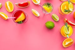 Tropical fruit cocktail with alcohol. Glass with beverage near oranges, grapefruit, lime and rosemary on pink background. Top view Stock Photo
