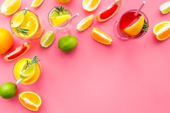 Tropical fruit cocktail with alcohol. Glass with beverage near oranges, grapefruit, lime and rosemary on pink background. Top view Stock Images