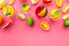 Tropical fruit cocktail with alcohol. Glass with beverage near oranges, grapefruit, lime and rosemary on pink background. Top view Royalty Free Stock Image
