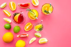 Tropical fruit cocktail with alcohol. Glass with beverage near oranges, grapefruit, lime and rosemary on pink background. Top view Royalty Free Stock Photography