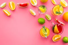 Tropical fruit cocktail with alcohol. Glass with beverage near oranges, grapefruit, lime and rosemary on pink background. Top view Royalty Free Stock Images