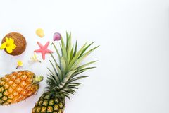 Tropical fruit composition with pineapples, coconut, flowers, shells and starfish. Summer vacation background concept. top view,flat lay Stock Image