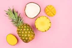 Tropical fruit flat lay on a pastel pink background. Corner orientation. Tropical fruit flat lay with pineapple, mango, and coconut on a pastel pink background Stock Photography