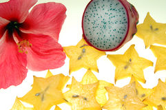 Tropical fruit and flower. Many pieces of sliced starfruit, dragon fruit and hibiscus on a white background stock photo