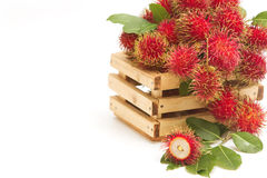 Tropical fruit, Fresh rambutans. In the crate Stock Photos
