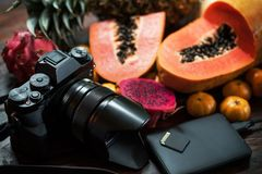 Tropical fruit near modern laptop on wooden background. Vegan lifestyle. stock images