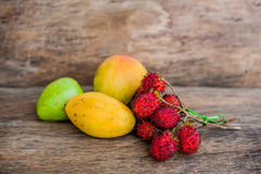 Tropical fruit on the old wooden background. Rambutan, banana, mango, guava. Tropical fruits concept Stock Images