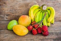 Tropical fruit on the old wooden background. Rambutan, banana, mango, guava. Stock Image