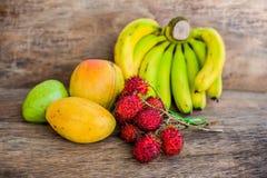 Tropical fruit on the old wooden background. Rambutan, banana, mango, guava. Stock Photos