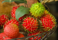 Tropical Fruit, Rambutan, Hawaii. A colorful green and red tropical fruit known as rambutan is sold by a farmer in a local farmer's market in Oahu, in the Stock Image
