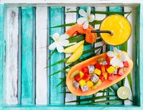 Tropical fruit salad in half of papaya mango juice. Tropical fruit salad in half of papaya with mango juice, smoothie. Top view. Copy space Stock Images