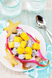 Tropical fruit salad in pitahaya, mango, dragon fruit bowls with a glass of juice Royalty Free Stock Photos