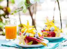 Tropical fruit salad in pitahaya, mango, dragon fruit bowls with a glass of juice Royalty Free Stock Images