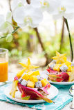 Tropical fruit salad in pitahaya, mango, dragon fruit bowls with a glass of juice Royalty Free Stock Image