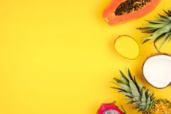 Tropical fruit side border on a bright yellow background. Tropical fruit side border with pineapple, dragon fruit, papaya, coconut and mango on a bright yellow stock image