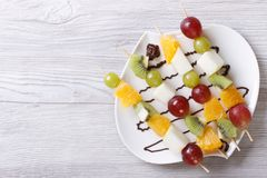 Tropical fruit on skewers with chocolate. horizontal  top view. Tropical fruit on skewers with chocolate sauce. horizontal view from above Royalty Free Stock Photography