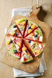 Tropical fruit watermelon pizza on a board. Overhead view of a colorful tropical fruit watermelon pizza topped with kiwifruit, blueberries, orange, pineapple Royalty Free Stock Image