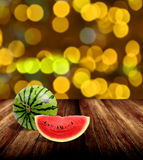Tropical fruit watermelon on wooden table with yellow bokeh Royalty Free Stock Image